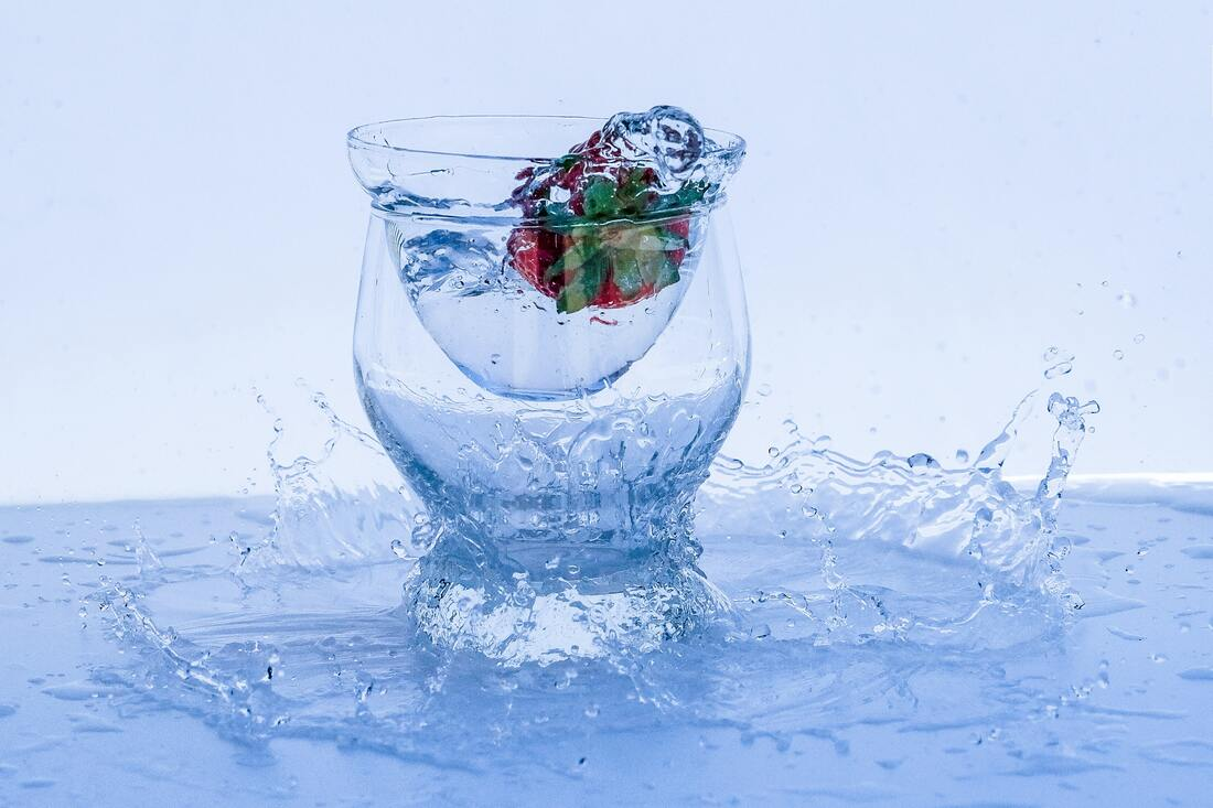 Water splashing out of a glass, displaced by a strawberry