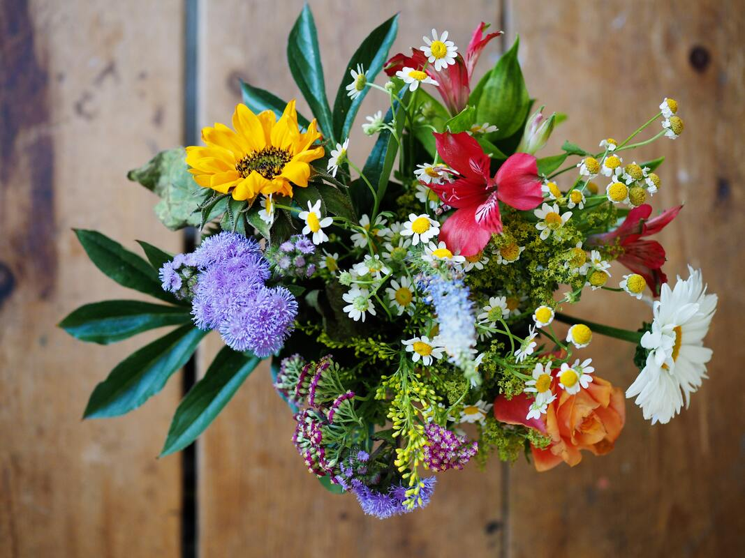 Bouquet of wild flowers on a wooden table viewed overhead