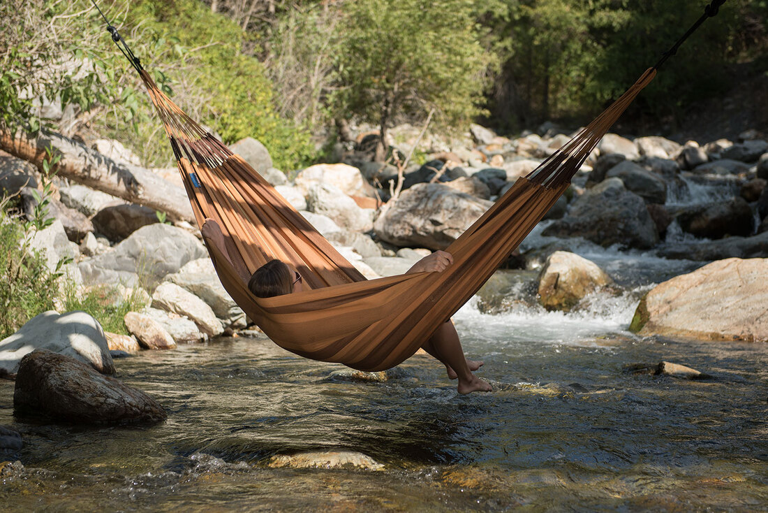 Woman relaxing in a hammock over a stream