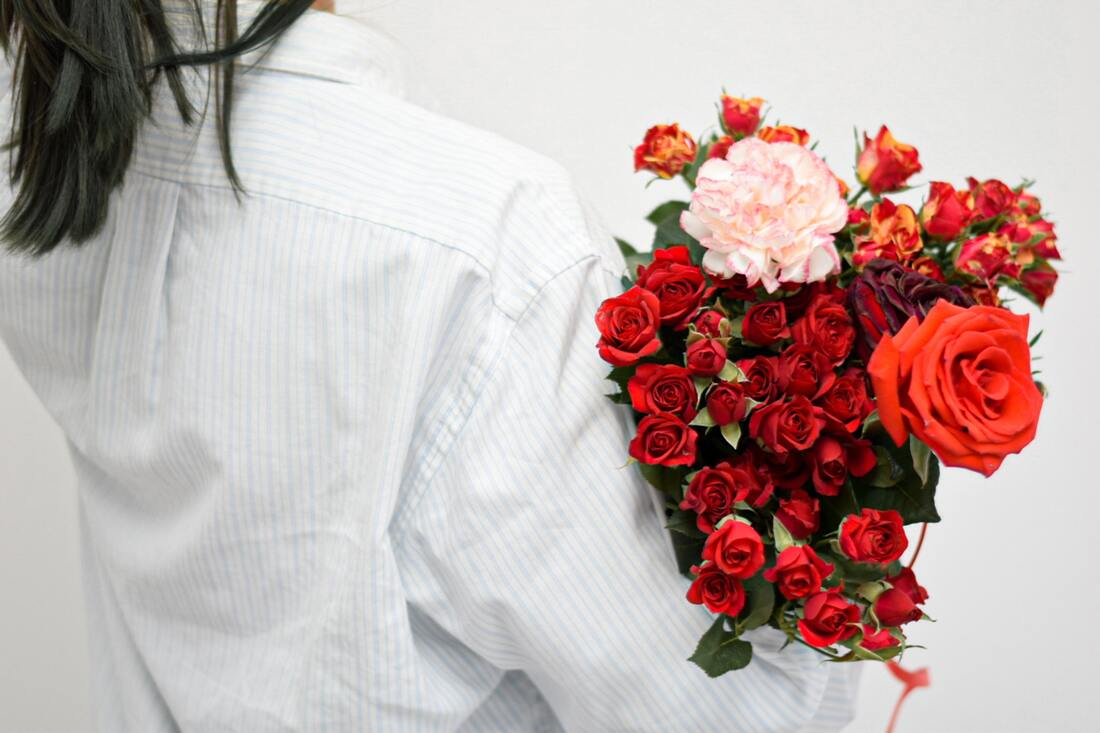 Side back view of woman carrying a bouquet of roses